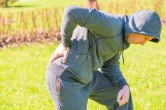 Mens die zijn hand pijnlijke rug houden Stock Foto's