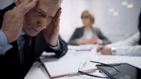 Mens die zijn die hoofd, migraineaanval houden door spanning, uitputting op het werk wordt veroorzaakt stock foto's