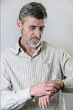 Mens die zijn horloge bekijkt Stock Afbeelding