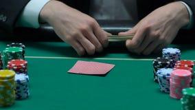 Mens die zijn kaart bekijken en op bureau grote som werpen geld, risico om te verliezen stock videobeelden