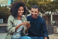 Mens die zijn meisje bekijken die mobiele telefoon met behulp van stock fotografie