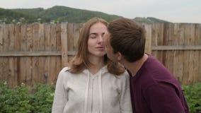 Mens die zijn meisje in de tuin kussen stock video