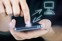 Mens die zijn mobiel en Desktop synchroniseren stock foto's