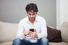 Mens die zijn mobiele telefoon met behulp van Stock Afbeelding