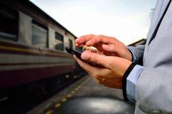 Mens die zijn mobiele telefoon op leeg spoorwegplatform met behulp van Close-up h Royalty-vrije Stock Fotografie