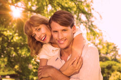 Mens die zijn mooi meisje een vervoer per kangoeroewagen in het park geven die bij camera glimlachen Stock Foto's