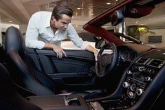 Mens die zijn nieuwe auto controleren royalty-vrije stock foto