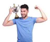 Mens die zijn spier buigen en een trofeekop houden stock foto