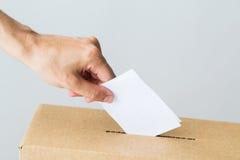 Mens die zijn stem in stembus bij de verkiezing zetten stock afbeeldingen