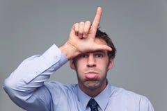 Mens die zijn tong plakt uit en verliezer gesturing Royalty-vrije Stock Afbeeldingen