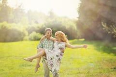 Mens die zijn vrouw op zijn wapens houden Stock Fotografie