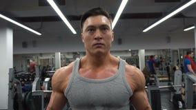 Mens die zijn wapens werken bij de gymnastiek Hij die de domoren opheffen en zijn bicepsen werken stock footage