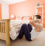 Mens die zitten-UPS in Slaapkamer doet Royalty-vrije Stock Afbeelding
