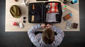 Mens die zorgvuldig koffer inpakken, die voor bedrijfsreis, officiële reis voorbereidingen treffen stock foto