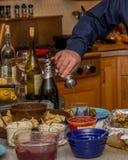 Mens die zout toevoegen aan zijn voedsel Stock Foto