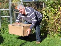 Mens die zware doos correct opheft. Stock Foto