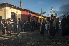 Mens die zwarte robes en kappen in een straat van de oude stad van Antigua dragen tijdens een optocht van de Heilige Week in Anti Royalty-vrije Stock Afbeeldingen