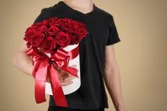 Mens die in zwarte t-shirt in hand rijk giftboeket van rood 21 houden Royalty-vrije Stock Foto's