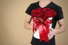 Mens die in zwarte t-shirt in hand rijk giftboeket van rood 21 houden Stock Afbeelding