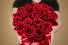 Mens die in zwarte t-shirt in hand rijk giftboeket van rood 21 houden Royalty-vrije Stock Afbeeldingen