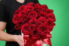 Mens die in zwarte t-shirt in hand rijk giftboeket van rood 21 houden Royalty-vrije Stock Afbeelding