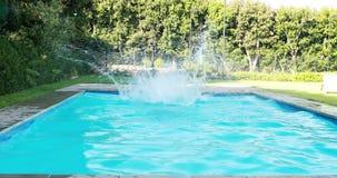 Mens die in zwembad springen stock video