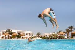 Mens die in zwembad springt Royalty-vrije Stock Afbeeldingen