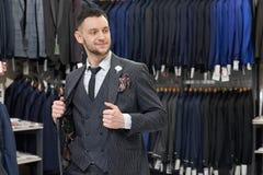 Mens doen die in boutique winkelen, die op grijs modieus kostuum proberen stock afbeelding