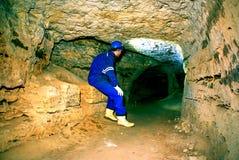 Mens in donkere oude tunnel, binnenspruit Treden aan tunnel met muren die van oranje steen worden gemaakt Royalty-vrije Stock Afbeeldingen