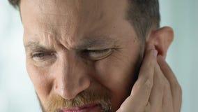 Mens door pijnlijke stuffiness in oorbesmetting of ontsteking, gezondheidszorg wordt gestoord die stock videobeelden