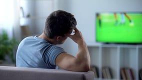 Mens door slechte kwaliteits digitale televisie wordt verstoord, vertraging van voetbalwedstrijduitzending die stock afbeelding