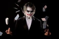 Mens in een beeld van een joker met kaarten stock fotografie