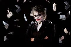 Mens in een beeld van een joker met vliegkaarten stock afbeelding