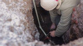 Mens in een gat in de aarde en het maken van noodsituatiereparatie van watersysteem Loodgieter die met grijze plastic pijp werken stock videobeelden