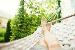Mens in een hangmat op een de zomerdag Stock Foto