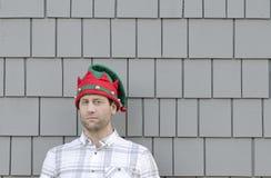 Mens in een Kerstmishoed die aan de kant met een grijnslach kijken Stock Fotografie