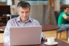 Mens in een koffiewinkel die aan laptop werken Stock Afbeeldingen