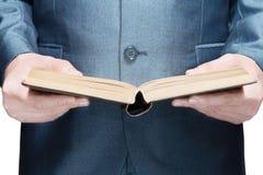 Mens in een kostuum die een open boek houden Stock Afbeeldingen
