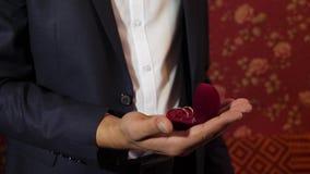 mens in een kostuum met gouden ringen in zijn hand De bruidegom houdt in zijn handdoos van gouden trouwringen stock footage