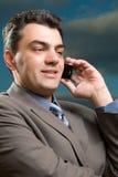 Mens in een kostuum met mobiele telefoon Stock Foto