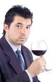 Mens in een kostuum proevende wijn Stock Afbeelding