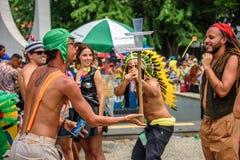 Mens in een kostuum van Inheemse mensen die die een boog en een pijl met zuignap in doel schieten van plastic koppen, Carnaval 20 royalty-vrije stock afbeeldingen