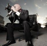 Mens in een kostuum zitting en het fotograferen Royalty-vrije Stock Afbeeldingen