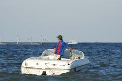 Mens in een motorboot stock afbeelding