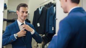 Mens in een nieuw kostuum bij kledingsopslag stock video