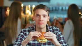 Mens in een restaurant die een hamburger en het glimlachen eten stock footage