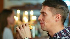 Mens in een restaurant die een hamburger eten stock video