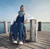 Mens in een rolstoel die op het overzees letten stock fotografie