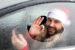 Mens in een rood GLB van Santa Claus in een auto met gebroken glas Royalty-vrije Stock Foto's