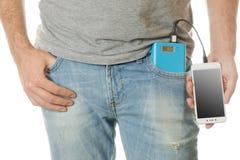 Mens in een smartphone van de zak mobiele telefoon en een machtsbank Royalty-vrije Stock Foto